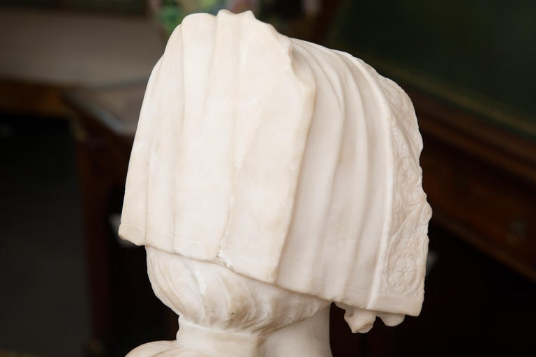 This is a delicate and gentle French Carrara marble sculpture of a young lady, wearing a lace head dress and cape. 19th century.