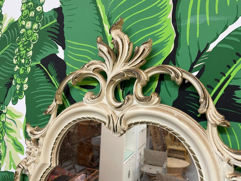 Ornate hand carved mirror by Syroco features intricate acanthus leaf scrollwork surrounding frame. Very good vintage condition with minor imperfections consistent with age.