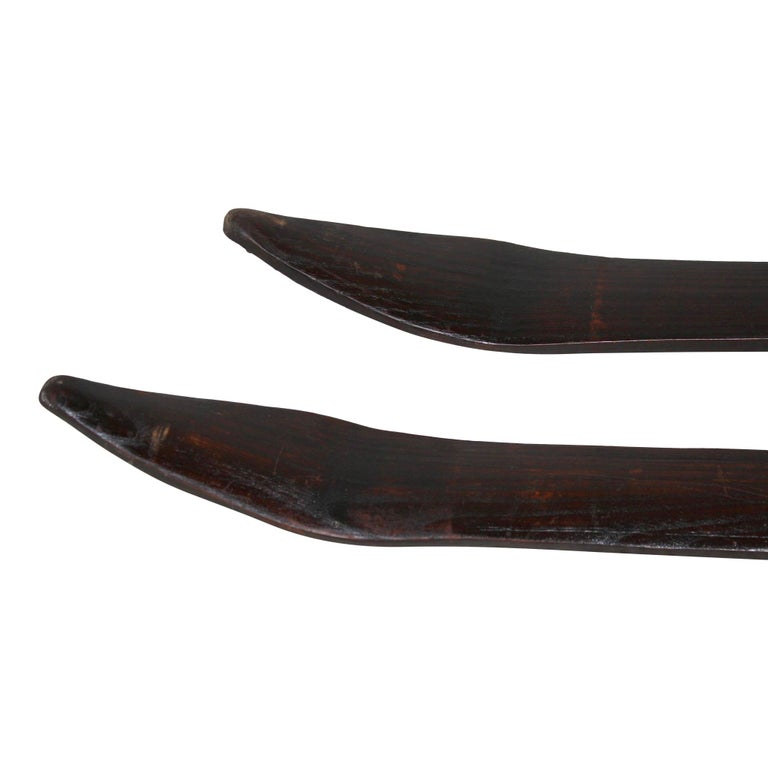 Hand carved from Scandinavia, this rare, long pair of ash skis is equipped with early leather bindings.