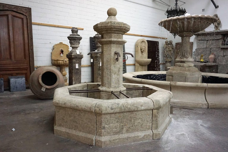 Here we offer a hand carved limestone central fountain with four iron downspouts. This fountain is a classical French design from an antique village fountain reclaimed outside Montpellier, France. The acoustics from this fountain will fill the air