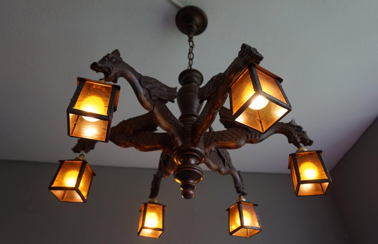 Antique wooden light fixture with dragons and hand forged, wrought iron lanterns.  This handcrafted, excellent condition chandelier comes with six stunning and well carved, winged dragon arms. Protruding like mediëval gargoyles on the ledge of a