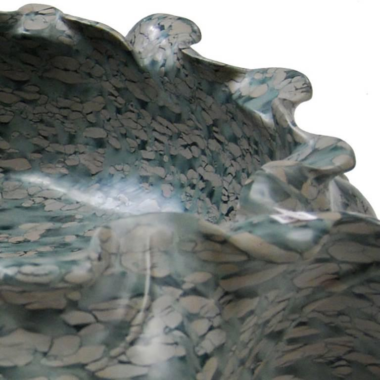 Hand-carved of mesmerizing puddingstone, this contemporary hand-carved stone basin evokes the graceful shape of a traditional lotus flower. Shaped with undulating curves, the container has the look of freeform pottery. Exploiting the stone's