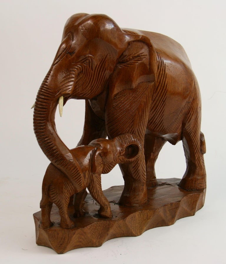 2-294, hand carved sculpture from a solid block of hardwood depicting a large elephant cradling a baby