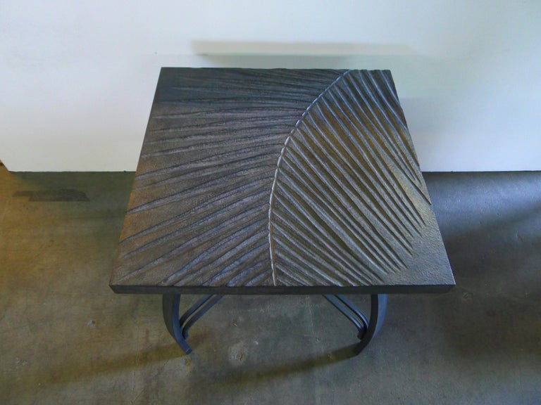Hand carved fossilized frond side table that can also be customized as a cocktail table. By order. Each tabletop is hand carved wood in gray slate coloration, and with iron base. Also can be placed outdoors in undercover location. Shown is side