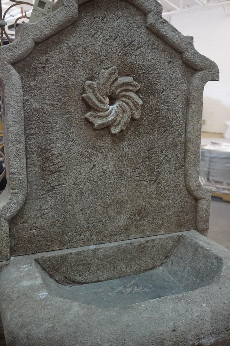 This hand carved wall fountain is made of limestone and features a floral motif surrounding the spout. Perfect for a quaint garden!  Measurements: 26