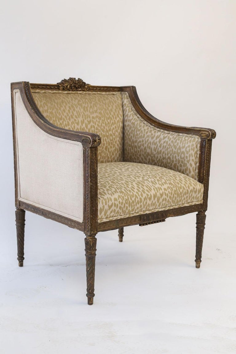 Hand carved Louis XVI bergere from France, upholstered in vintage fabric. This 18th century French armchair is hand carved in fruitwood (probably walnut) circa 1775-1795 with remnants of darkened gilt and gesso.