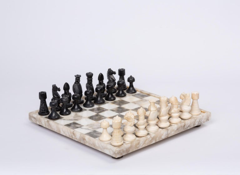 Hand carved marble and bone chess set. This stunning monochrome set features a marble checkerboard inset into a thicker marble frame, which sits atop short marble feet. The intricate chess pieces are hand carved marble and bone, and compliment the