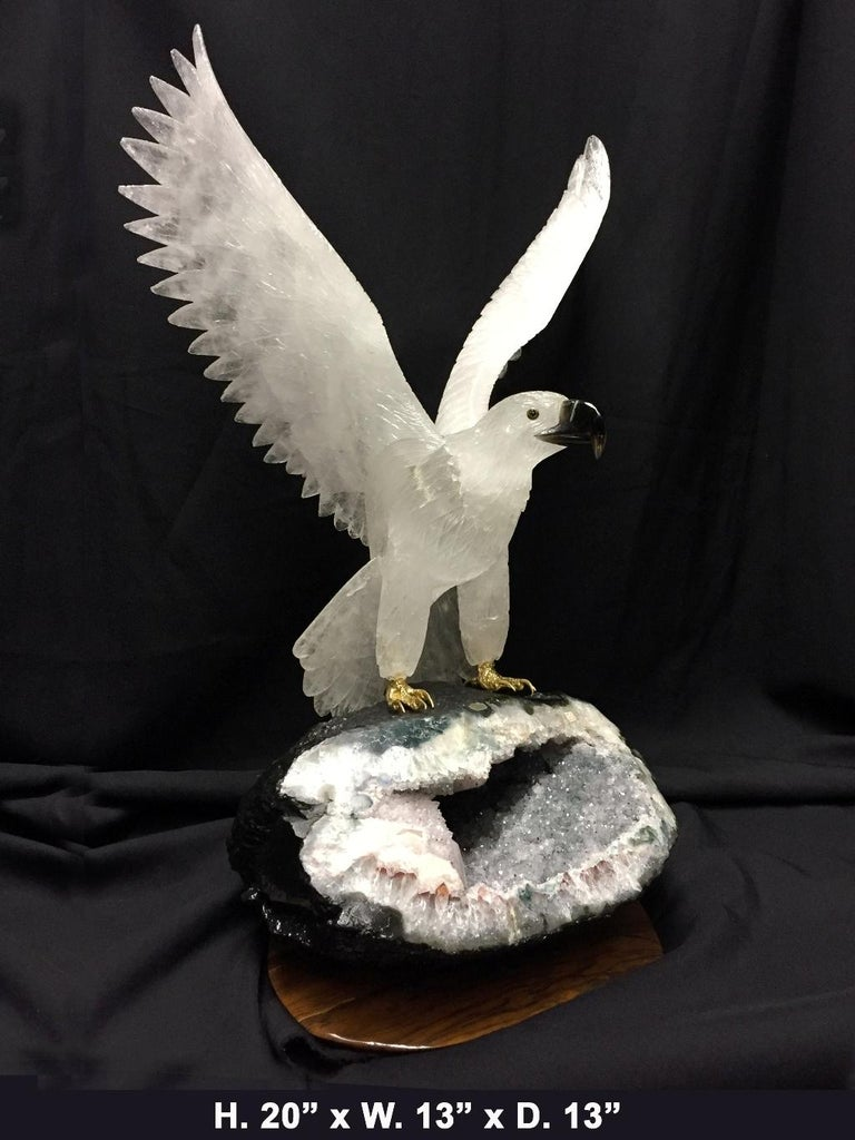 Magnificent one of a kind large finely hand-carved and hand polished rock crystal eagle with spread wings and black obsidian eyes and beak on beautiful a Amethyst Geode base, all resting on a brown gemstone base.