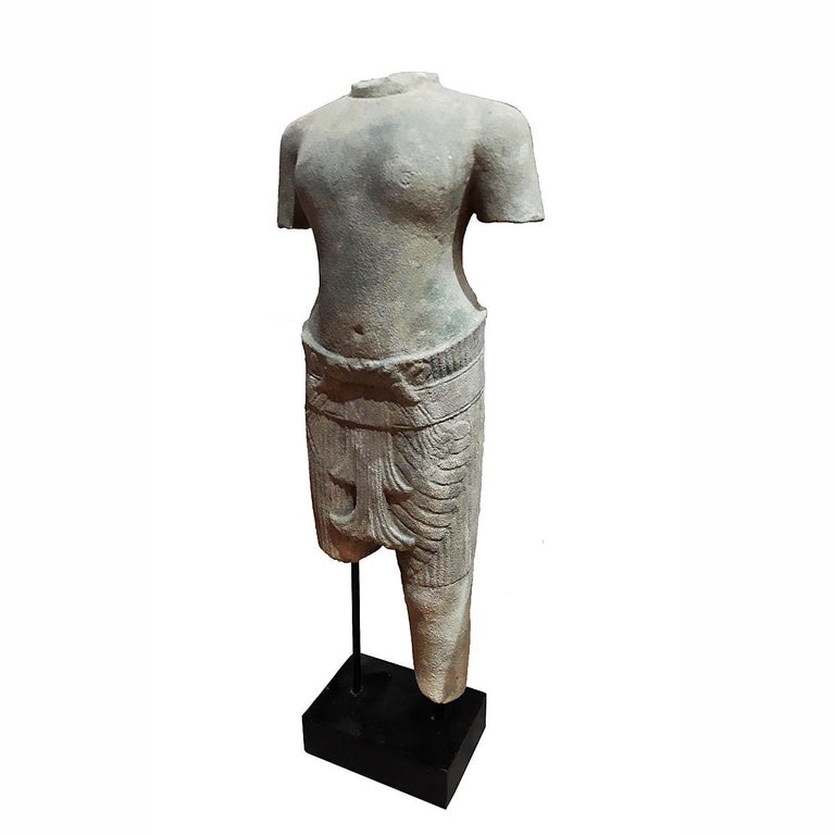 A sculpture of a male torso in traditional attire, hand carved from a single piece of sandstone. From Thailand. Mounted on a wood / metal stand. At 28 inches high, this torso makes an eye-catching accent for a table, console or desk.