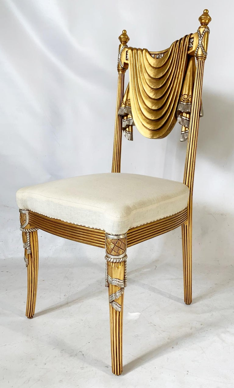 Hand carved dining chairs feature swag back motif in the form of draped fabric with tassel accents. Hand carved in Syria. Available in bright gold finish, as well as antique gold and a brown stained finish as well. Seats are ready for your custom