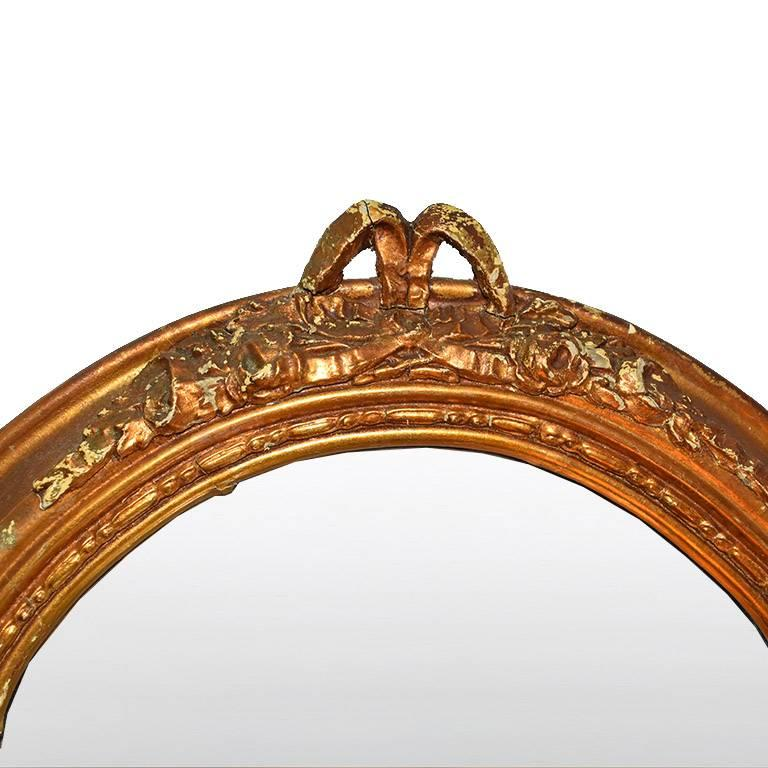 Long tall giltwood mirror with gold hand-carved rosette and floral moulding around the edges. The top of the piece features a bowl and bottom edges are rounded. Would make a wonderful addition to any space, or a great piece for creating a gallery