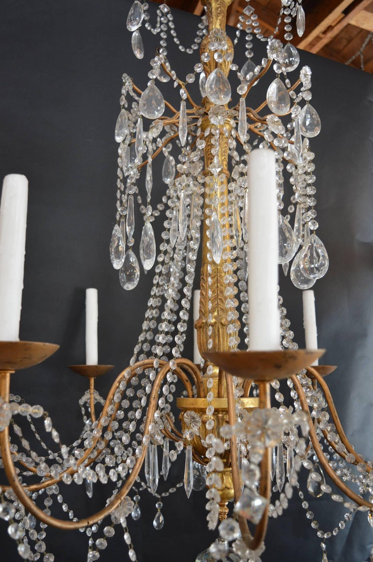 Hand-carved wood with metal arm and crystals.