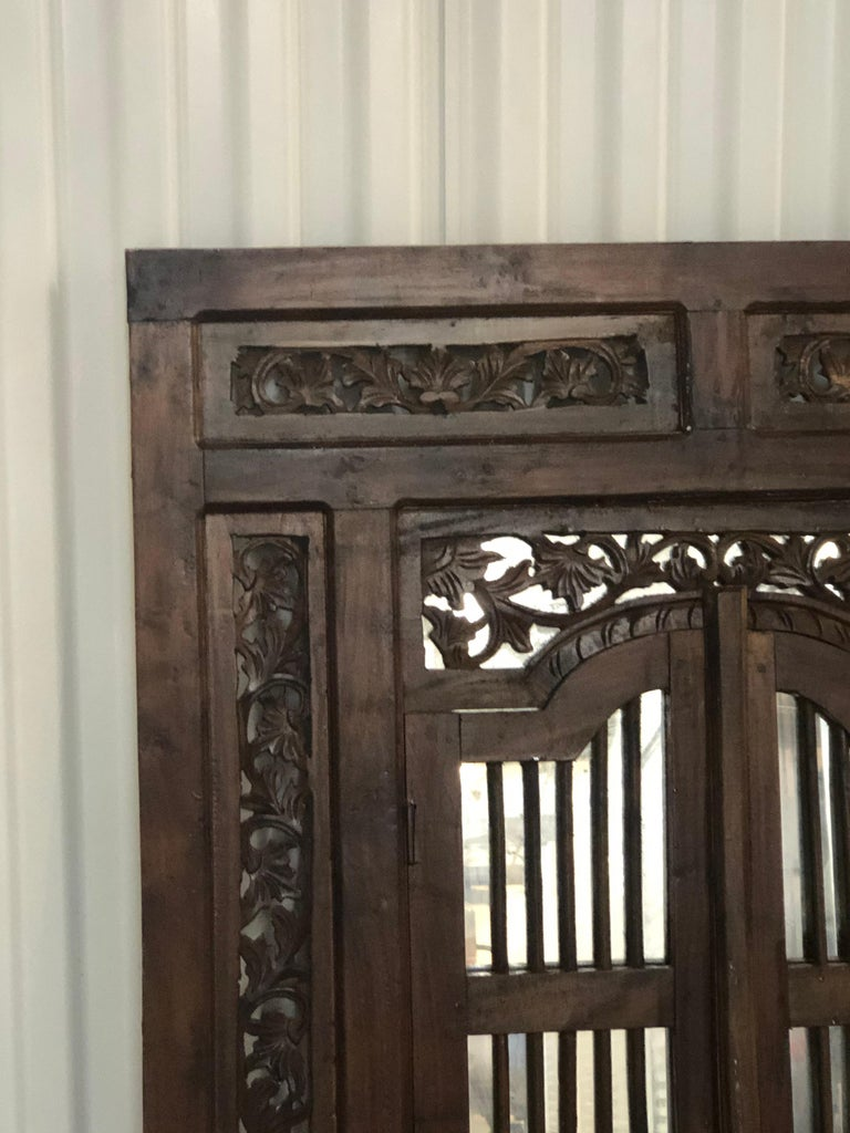 Hand Carved Wood Indian Wall Mirror. Heavy wood carved mirror depicting flowers and vines all around. New mirror inset and pair of wooden windows that open out. Hanging wire in the back. Size: 31.5
