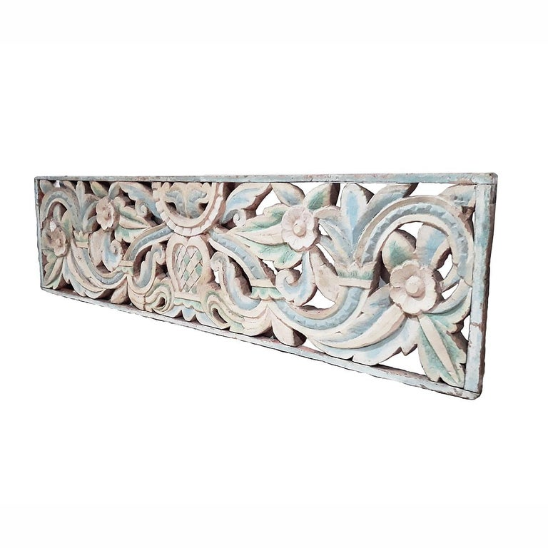 An early 20th century teak wood panel from Indonesia, intricately hand carved and polychromed in white and light blue. Floral motif, circa 1900.