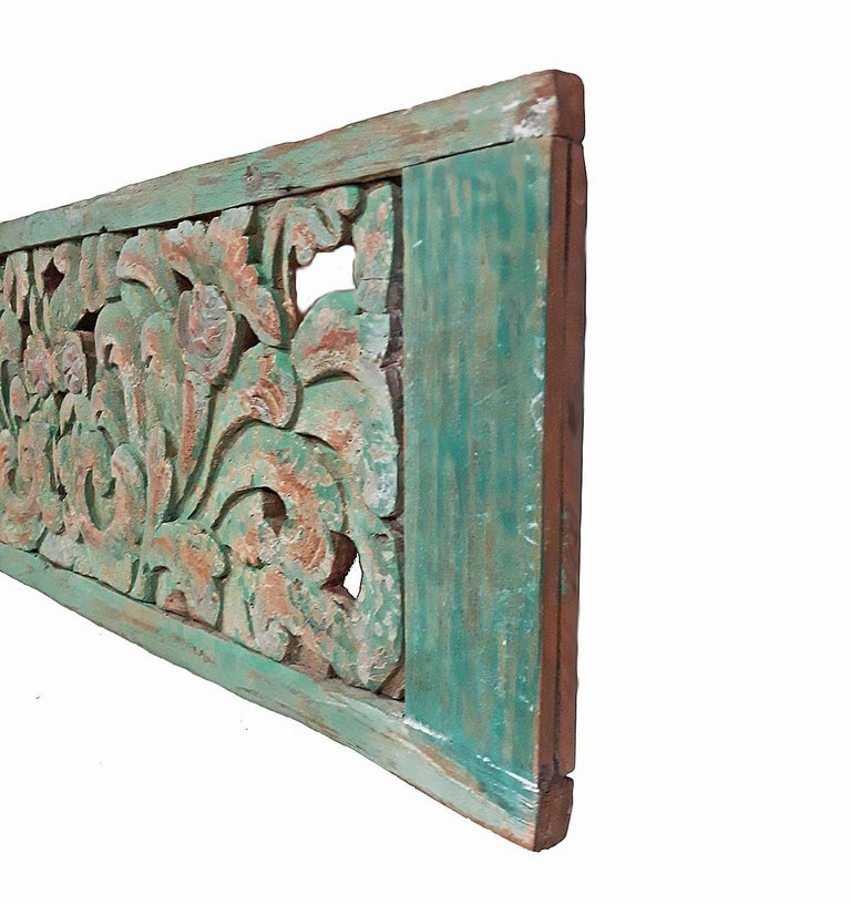 An early 20th century teak wood panel from Indonesia, intricately hand carved with a floral motif and polychromed in deep green, circa 1900.