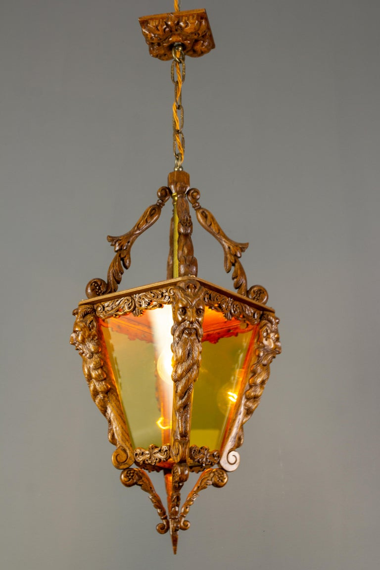 A beautiful and finely hand carved wooden lantern with yellow glass, Belgium, circa 1960s. Masterful carved wooden details such as acanthus leaves and four Bacchus heads on each corner of the lantern feature exceptional carving workmanship. Even the