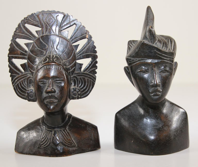 Vintage midcentury hand carved ebony wooden Balinese busts sculptures. Hand carved sculpture in wood depicting a Balinese couple. Bust of a man and women in Art Deco style sculpture wearing traditional ceremonial head dress, great