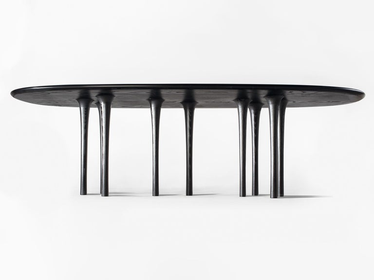 Hand-carved wooden dining table by Hudson Valley-based artist and designer Christopher Kurtz, with delicately-shaped hollow legs and beautifully sculpted surface. Shown in ash with black aniline dye. This work is customizable in size, wood species