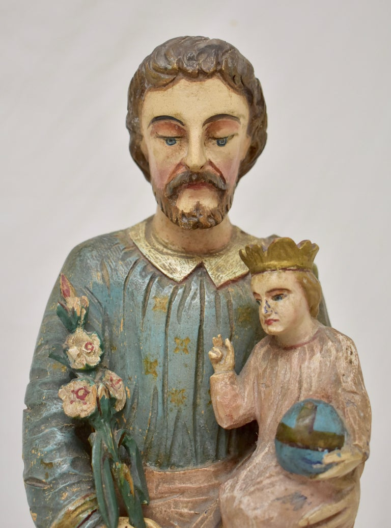 This is a striking Primitive hand carved statue of Saint Joseph.  The Saint stands with head slightly bowed and with a reverent expression. He is clothed in a long blue tunic bearing pressed, gold-painted floral buds, beneath a green toga, slung