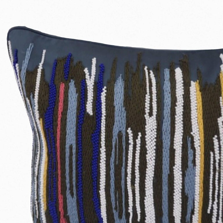 Hand embroidered pillow. Handcrafted using Matt beads and cotton yarn embroidered in multicolored stripes on a blue background. Satin fabric,self zip and feather pads.