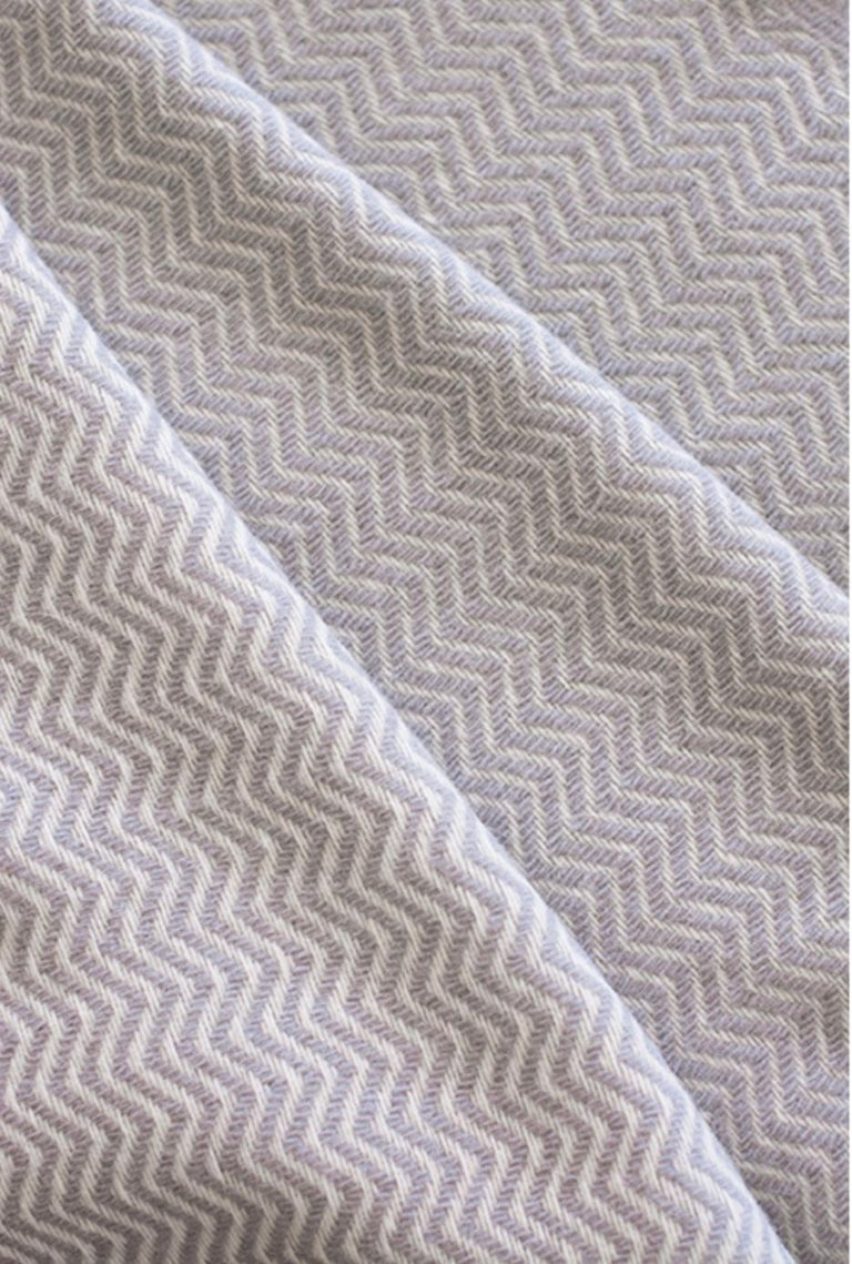 The Otilia hand finished organic wave design wool blanket/throw has been created by an incredible and unique family owned weaving and textile company in Portugal. This company impressed us so much by their commitment to working with the environment,