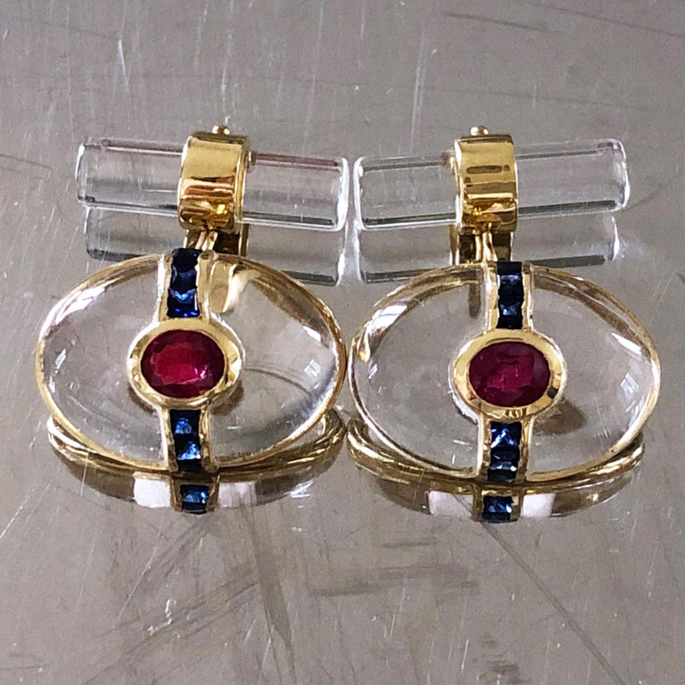 One-of-a-kind absolutely Chic yet Timeless pair of Cufflinks featuring an Oval Hand Inlaid Rock Crystal Cabochon embracing a natural Oval Ruby and an almost 1 Carat Blue Sapphire Calibré Cut Line, 18K yellow Gold Setting.  A Rock Crystal Stick back