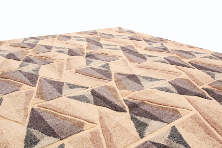 Originating from India, this geometric rug is hand knotted in high-quality wool with an all-over field design blending influences from prismatic patterns and Mid-Century Modern color sensibilities. Depicted in an all-over, borderless field design,