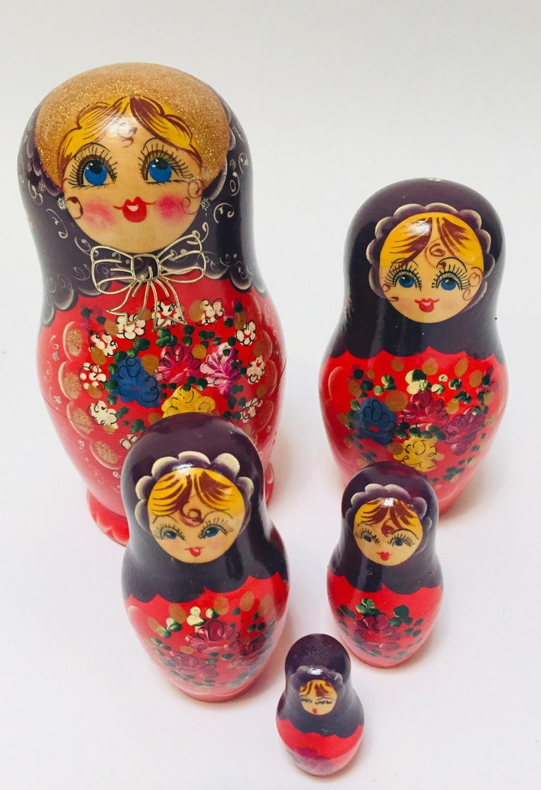 Vintage hand painted and carved nesting dolls in traditional costume, woman wearing head scarf and traditional robe with baby girls. Traditional hand painted beech wooden Matryoshka nesting dolls. This Matryoshka dolls are made of beech wood with
