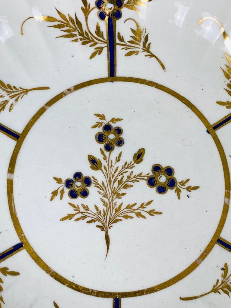 This exquisite late 18th-century dish features several elements that make it so full of life. First is the splendid hand-painted goldwork. This gilding enlivens the dish with its hand-painted golden vines, leaves, and edge. Additionally, the lovely