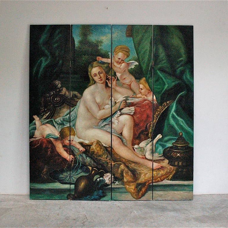 A four part folding screen or room divider. The four panels are covered in a hand painted canvas depicting a traditional classical scene of a young female, most likely Venus, surrounded by three cheeky cherubs. Although facing a mirror, the female's