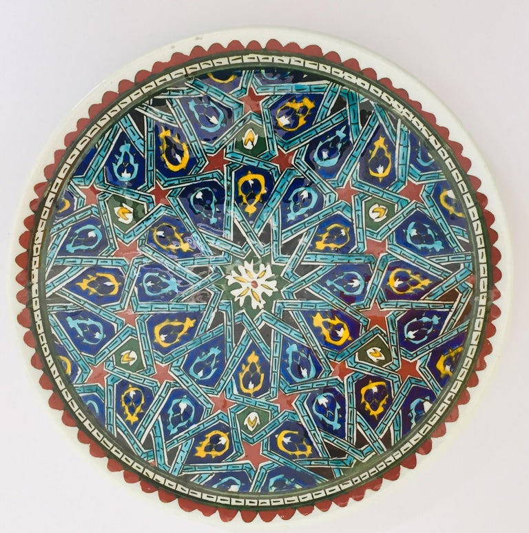 Polychrome hand painted and handcrafted ceramic wall decorative plate with polychrome Ottoman floral design. This is an intricately, hand painted Moorish plate that was made in Turkey. Turkey is famous for its kiln products, such as tiles and