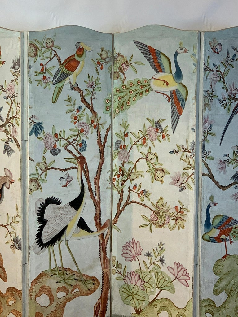 A beautifully painted early 20th century four panel folding screen in the style of Gracie or de Gournay wallpaper depicting exotic colorful birds set amid flowering trees.