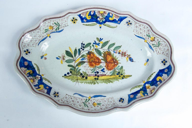 Hand painted French faience platter, early 19th century. Scalloped, oval shape. Center floral and border designs in traditional coloration.