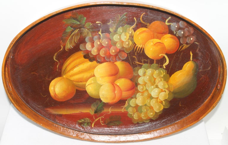 Hand painted wood fruit serving tray with double handles. The condition is very good. It looks like a very well done still life.