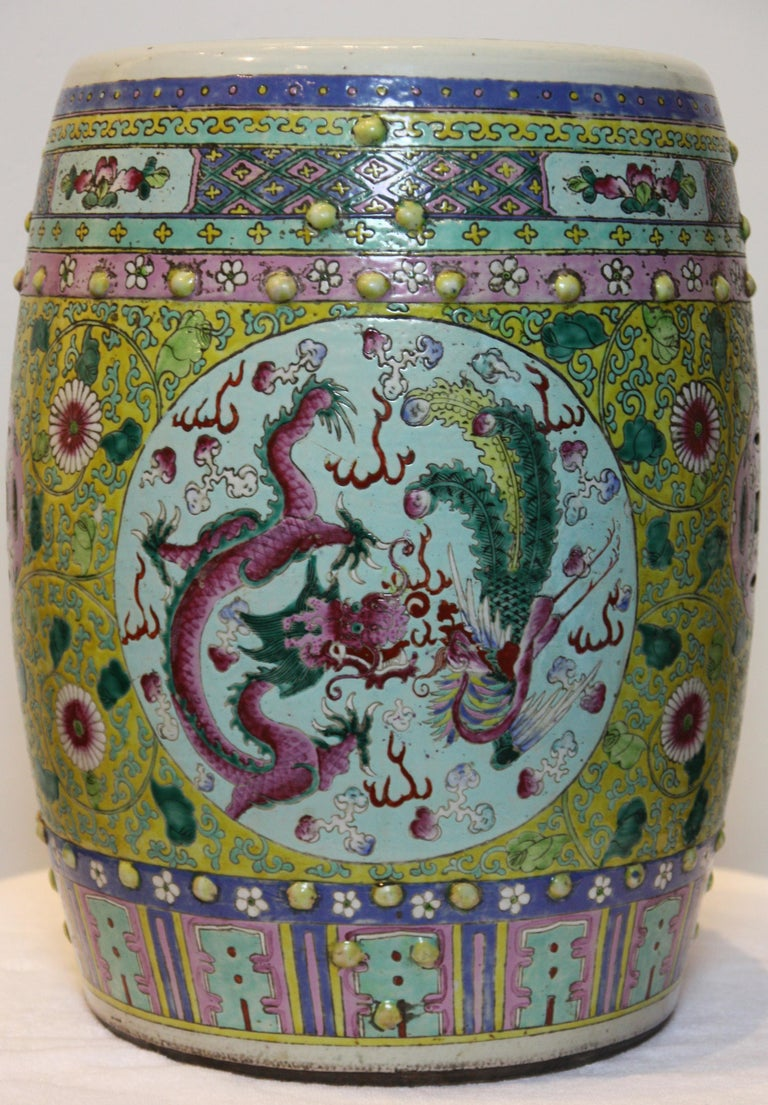 Bright and colorful hand-painted garden seat. Intricate design and images of dragons, flowers and other plants.