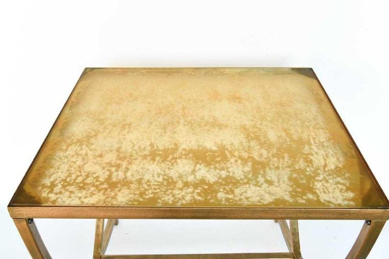 A hand painted gold metal and glass side table in the Art Deco style. The conforming hand painted top rests on U-shaped bases at either end with a cross-stretcher for support and terminates in rectangular brass feet. Contemporary. Dimensions: H 22