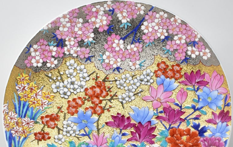 """Entitled """"Spring in Full Bloom,"""" this extraordinary contemporary Japanese porcelain charger/centerpiece features a rich tableau of spring flowers in full bloom. The charger is intricately hand painted in a full range of colors set against an"""