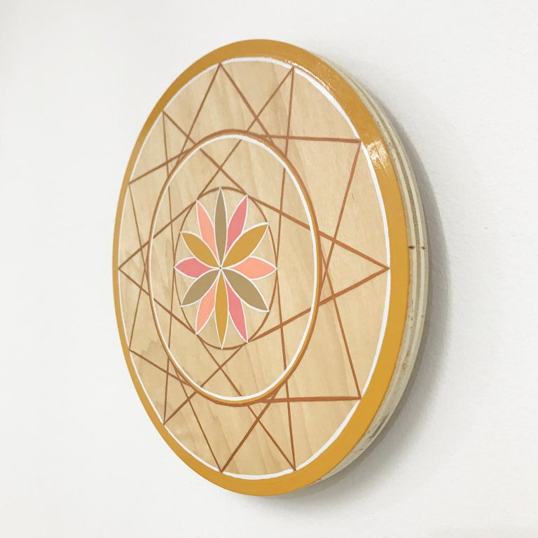 """This wall hanging by Scott Chasse is adorned with a hand-painted pink, peach and gold toned design rooted in the sacred geometry of the flower of life.   One-shot enamel hand-painted on plywood  Measures: 11.75"""" diameter, painted on 3/4"""" plywood"""
