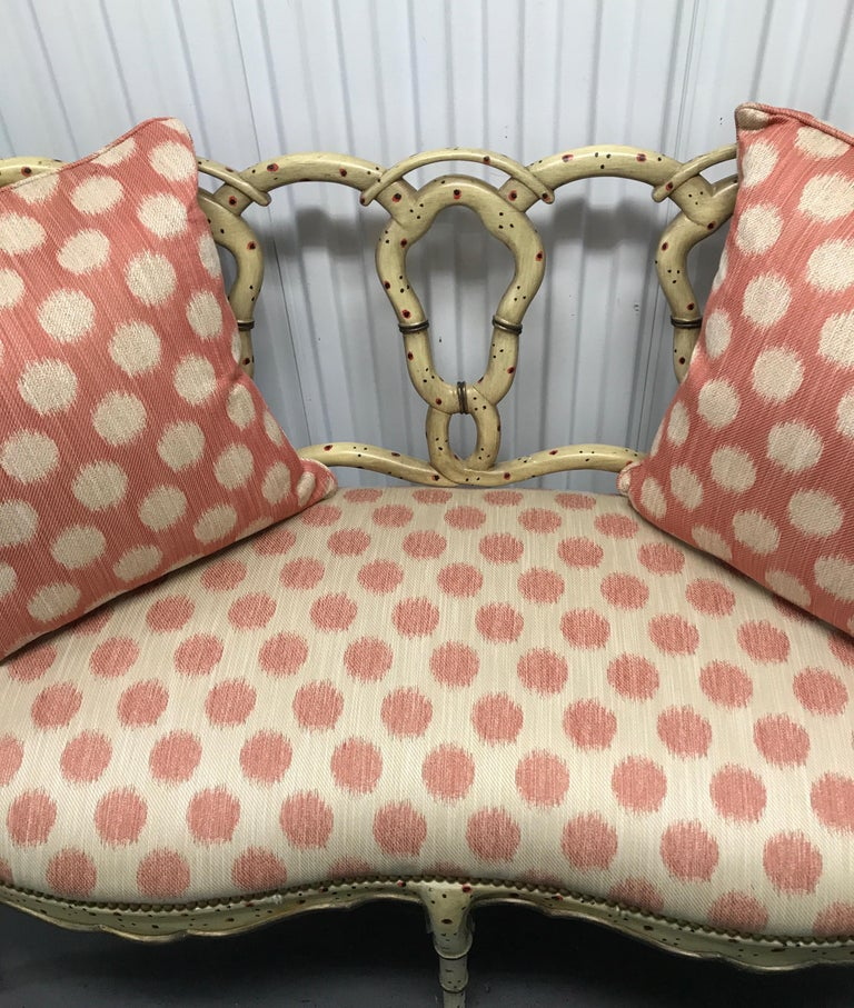 Whimsical hand painted wood loveseat with twisted pretzel back and upholstered seat.