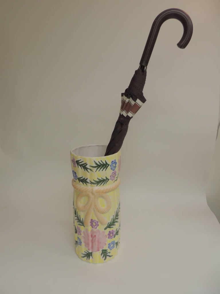 Hand-painted round Palm Beach chic ceramic umbrella stand with bow and tassels, hand painted flowers around. In shades of yellow, green, pink, peach and purple. Size: 7.5 x 7.5 x 17.5.