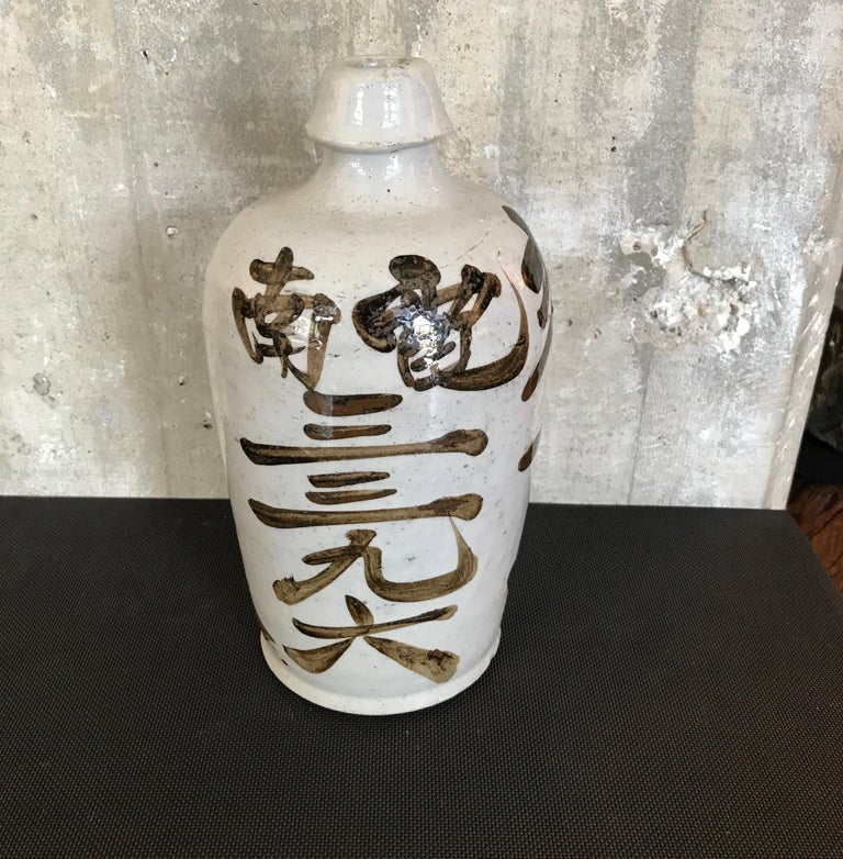 A beautifully glazed and hand painted Japanese sake bottle with gorgeous calligraphy on all sides. A wonderful shelf piece, Japan, circa 1960. CR1006b.