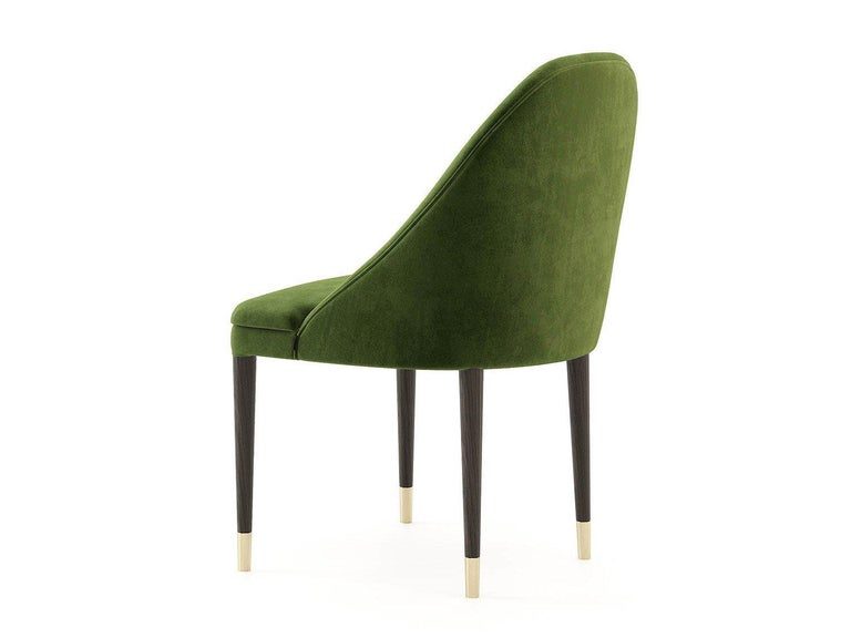 This piece is a mid-century dining chair with a modern twist.? Handmade from the finest materials with a crescent back and upholstered in green velvet.? Frame in black oak finish with golden caps. Suitable for contract use. 100% European made