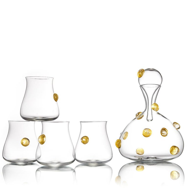 The Festa collection of hand blown glass decanters and barware features a celebratory, golden confetti pattern of optic glass dots. Encased gold leaf is magnified by the raised dot pattern, and decorates the surface of each carafe and tumbler. A