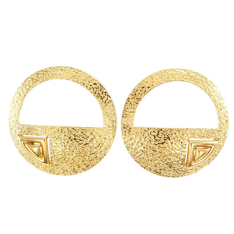 Handcrafted art studio 18 karat gold earrings by Frank's. The matching left and right, circular designs feature an upper, cut out, negative space and a lower, solid, positive space, decorated by reoccurring, triangular shapes overlaid on a shiny