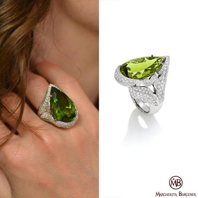 Handcrafted in Margherita Burgener family workshop, based in Italy, the Leave ring is centering an impressive, clean, deep saturated green peridot. The stone is hugged by a several leaves motif, pavé set in high quality diamonds.  18 KT white gold