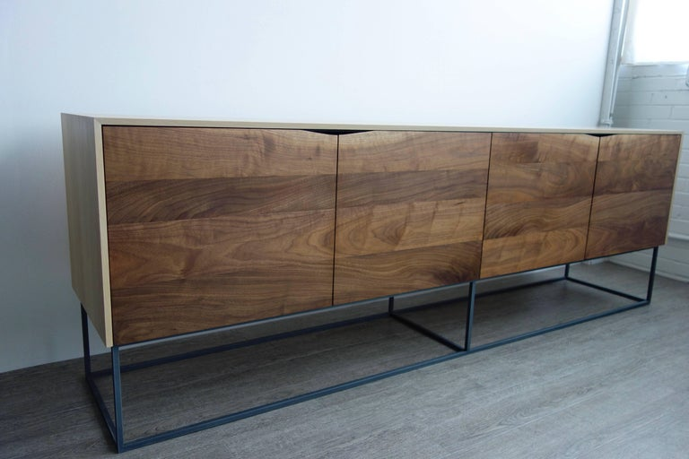 Handcrafted classic modern credenza of select white oak and walnut with a cold-rolled steel base. The exterior of the white oak cabinet is finished with a durable natural product that gives it a raw appearance; the interior is coated with a charcoal