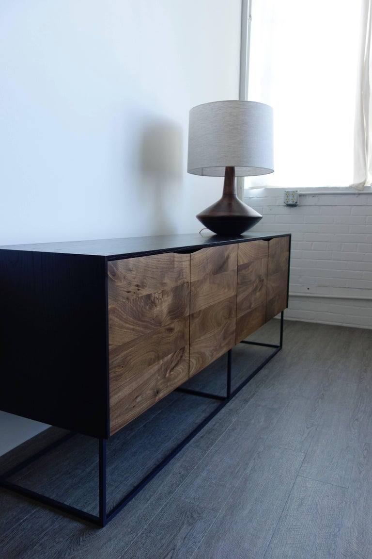 Handcrafted classic modern credenza of ebonized ash and walnut with a cold-rolled steel base. The exterior is ebonized and coated with a durable lacquer; the interior is coated with a proprietary deep blue colored lacquer. The soft-close walnut