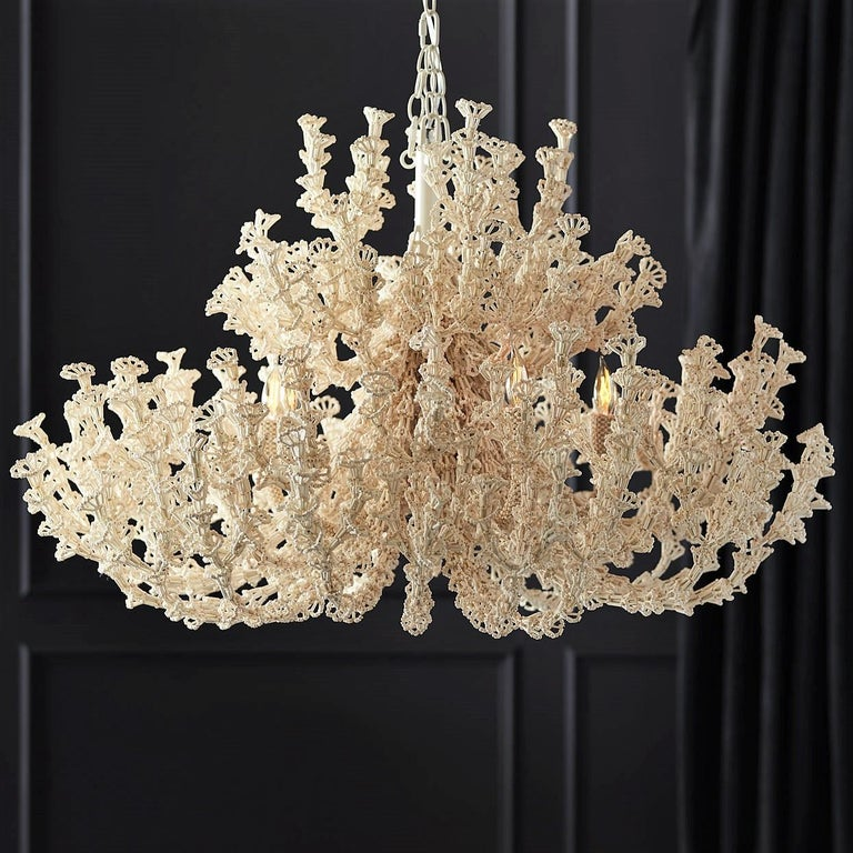 Feminine chandelier crafted from coco beads in soft cream finish.