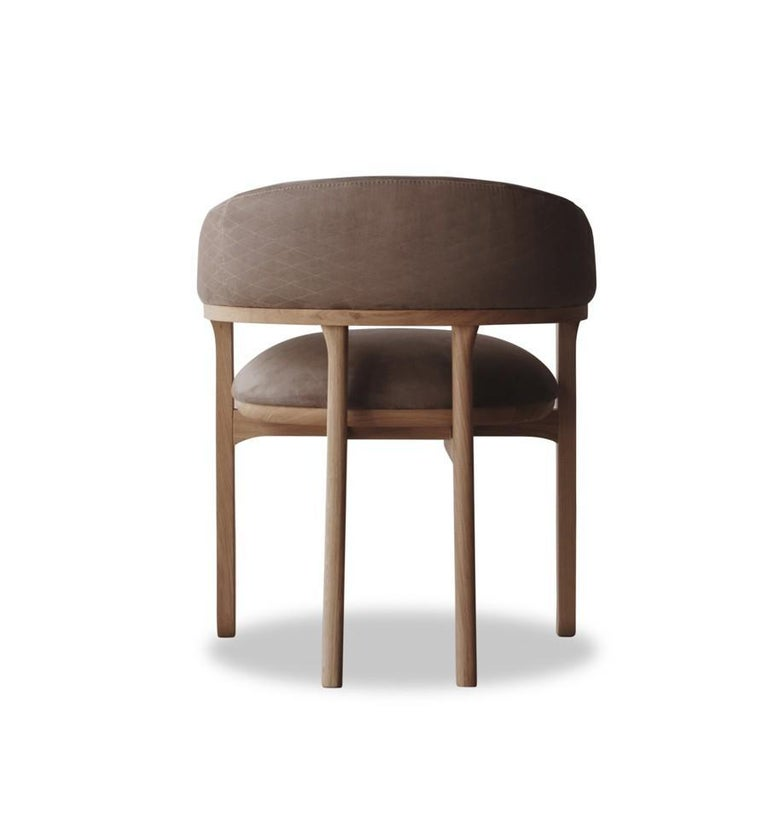The modern dining chair features an unusual shape and structure made of solid oak. This chair combines comfort and elegance with its very special thick seat and stylish character. Fabric: Smooth velvet Measures: Length 25.20