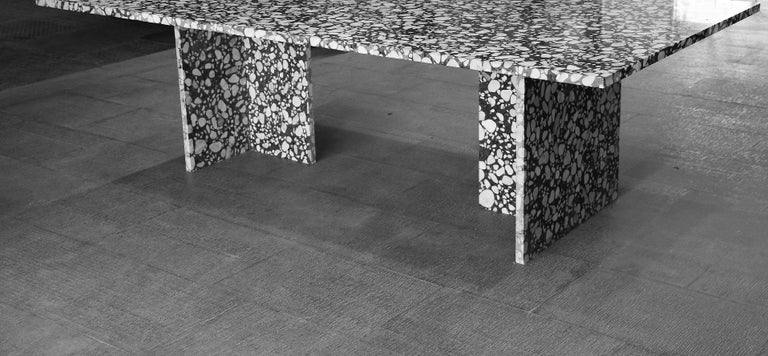 The different curves on the terrazzo top and the thin metal legs gives the impression that the table top rests on only one point as if it were levitating into thin air. The black stone background provides stark contrast to the white and grey marble